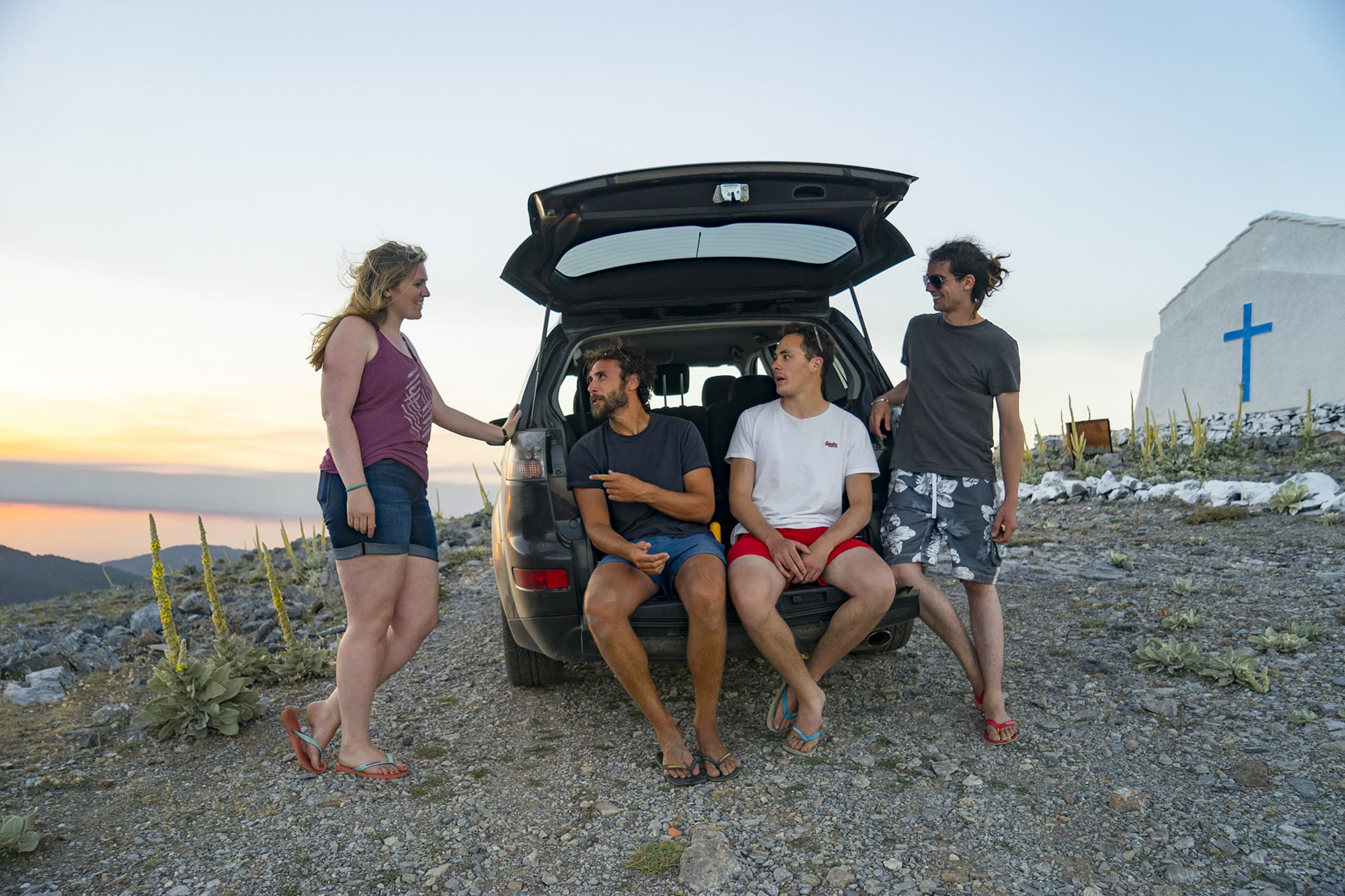 Friends exploring Samos by car and taking a break as the sun sets