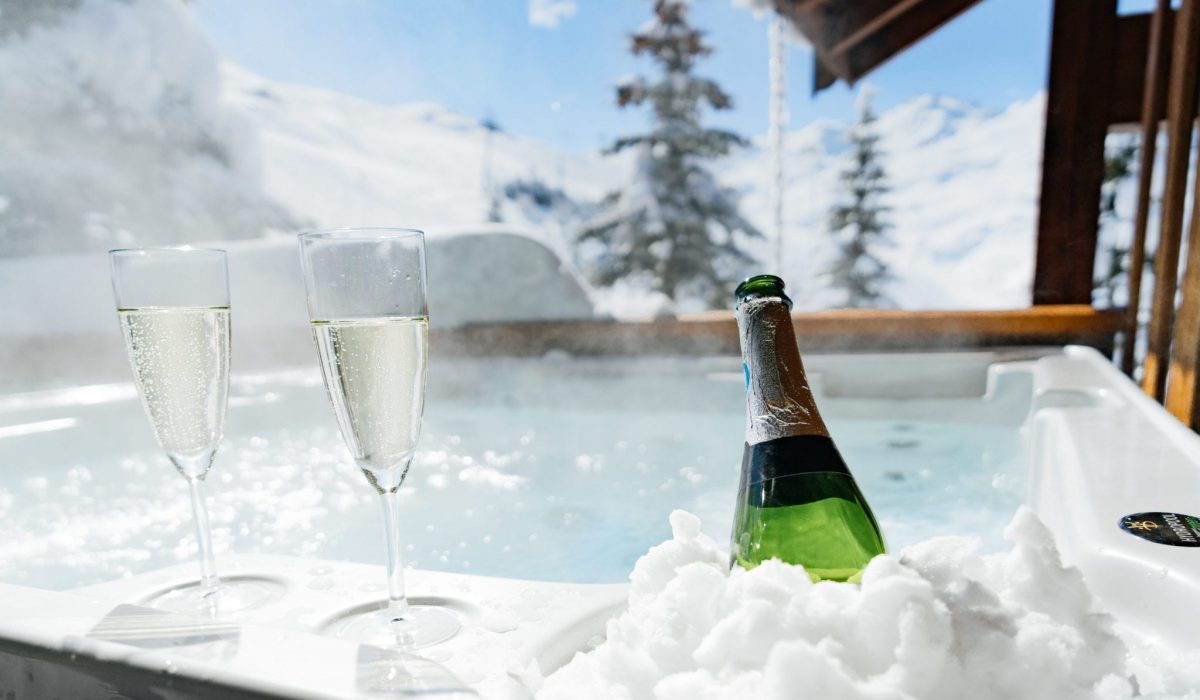 Champagne in the hot tub surrounded with snow and looking out over the ski slopes