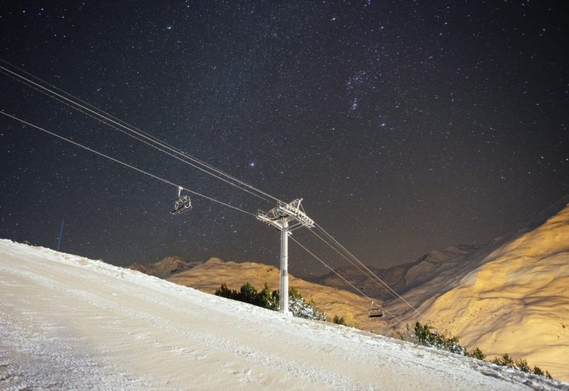 The night sky full of stars over the snowy mountains of the Three Valleys
